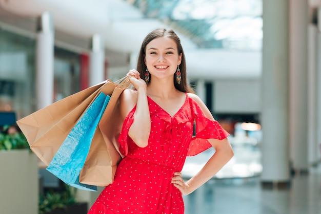 ファッションの女の子がショッピングセンターでポーズ