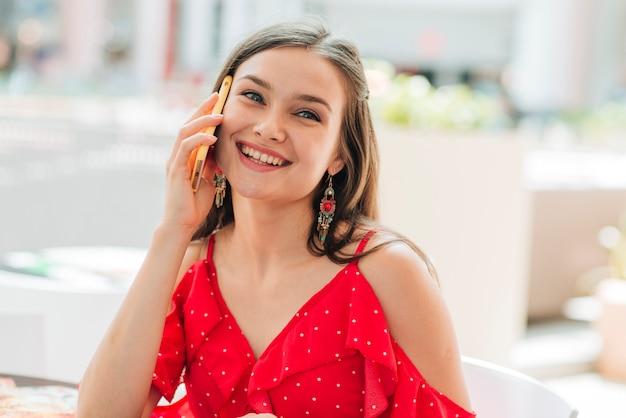 Вид спереди красивая девушка разговаривает по телефону