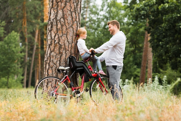 Отец держит дочь на велосипеде