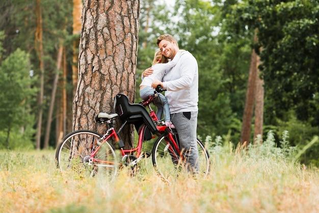 Отец обнимает дочь на велосипеде
