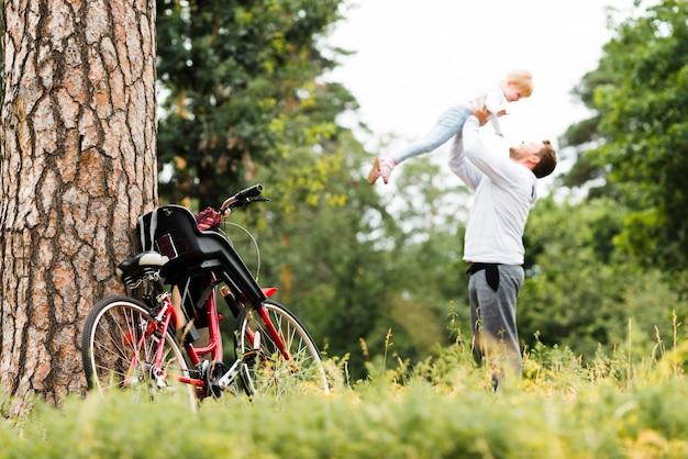 Отец держит дочь в воздухе