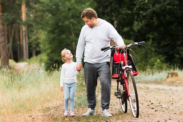 Отец и дочь гуляют рядом с велосипедом