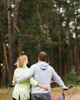背面の森の背景を持つカップルを抱き締める