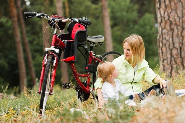 母と娘は自転車の横にリラックス