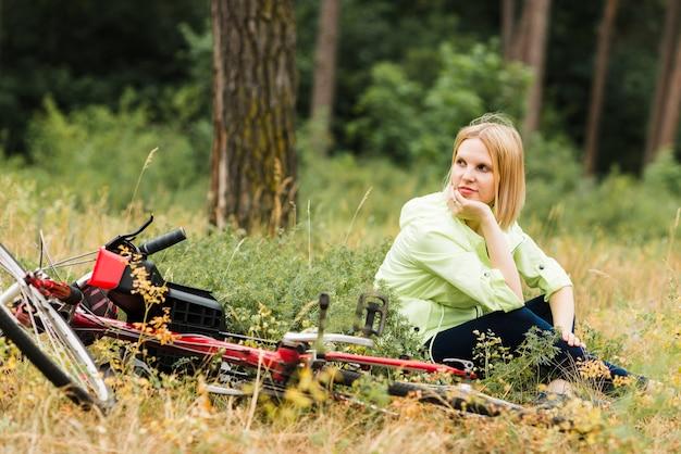 自転車の隣に座っているとよそ見女性