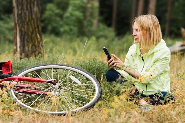 地面に座っていると携帯電話を見ている女性