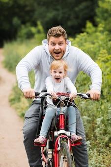 Счастливый отец и дочь на велосипеде