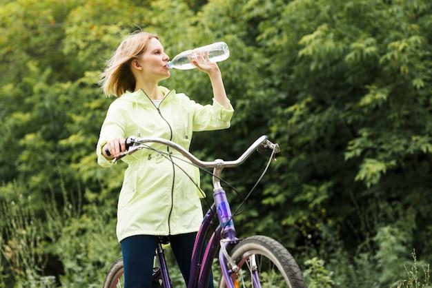 女性は自転車に水を飲む
