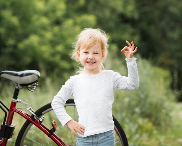 Маленькая девочка делает хорошо знаком перед велосипедом