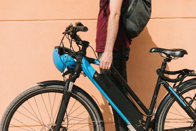 Городской велосипедист стоит рядом с электронным велосипедом