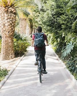 Вид сзади человека, езда на велосипеде на велосипедной дорожке