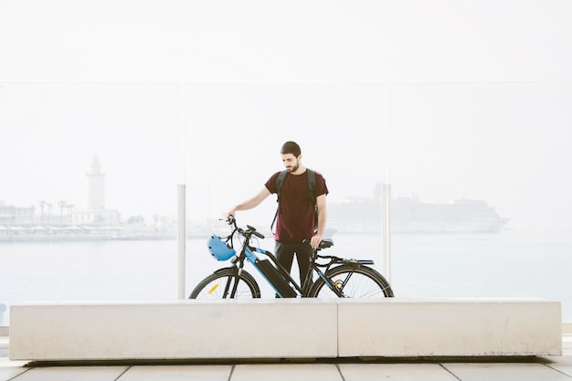 Длинный выстрел человек, стоящий рядом с электронным велосипедом