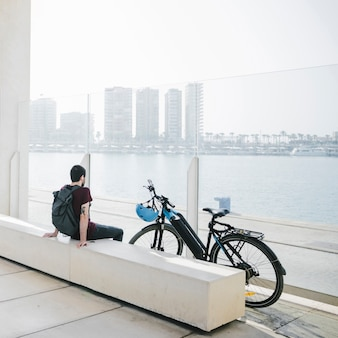Вид сзади человека, сидящего рядом с электрическим велосипедом