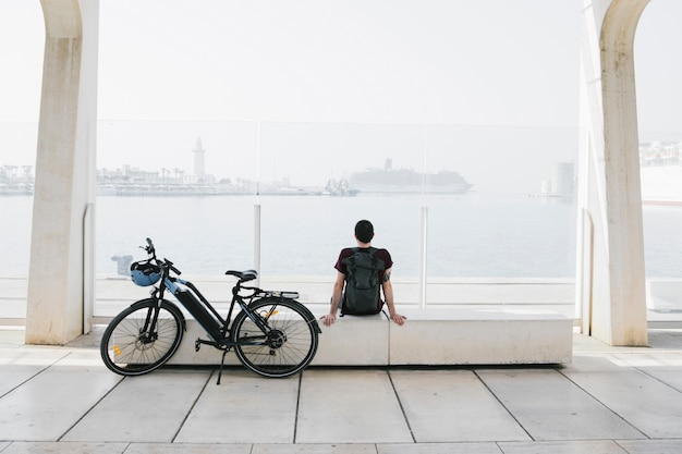 Длинный выстрел электронного велосипеда рядом с расслабляющим человеком на скамейке