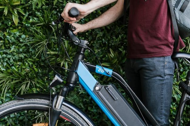 Крупным планом боком велосипедист держит электронный велосипед с зеленым фоном стены