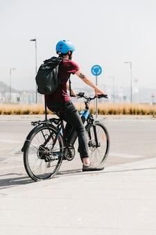 Вид сзади велосипедист ждет на остановке