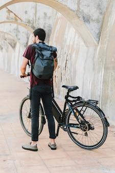 Вид сзади человека, стоящего рядом с электронным велосипедом