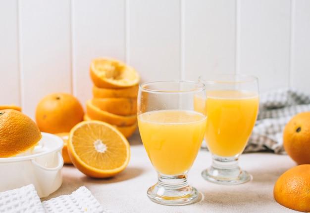 メガネで正面の新鮮なオレンジジュース