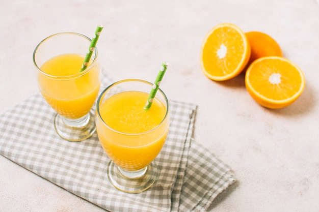 Высокий угол свежих апельсиновых соков на ткани