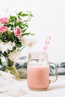 バラの花瓶の横にあるピンクのスムージー
