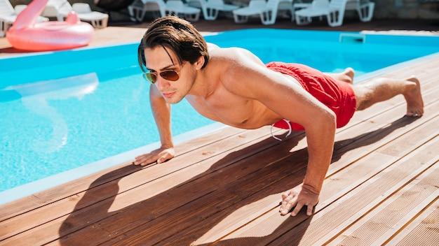 Человек в бассейне делает отжимания