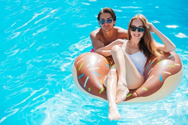 ドーナツ水泳リングでポーズをとるカップル