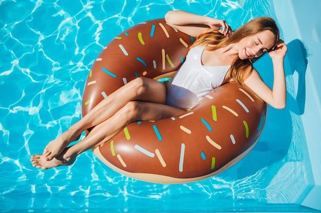 Женщина позирует в бассейне с закрытыми глазами