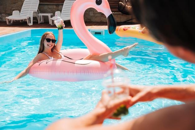 Мужчина наблюдает за женщиной в фламинго плавать кольцо
