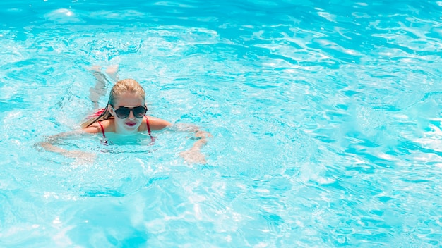 金髪の女性がプールで泳いで