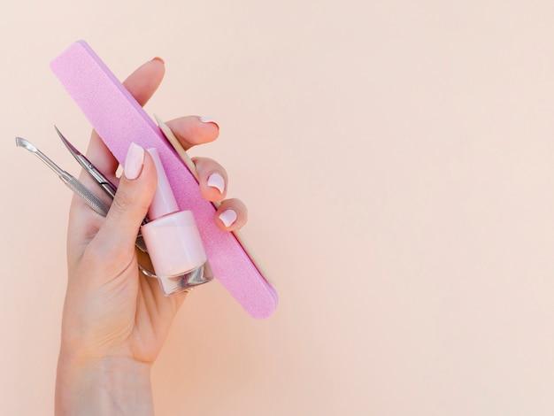 Рука женщины держа инструменты маникюра