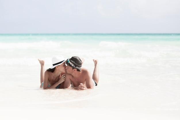 海辺でカップルのキスのロングショット