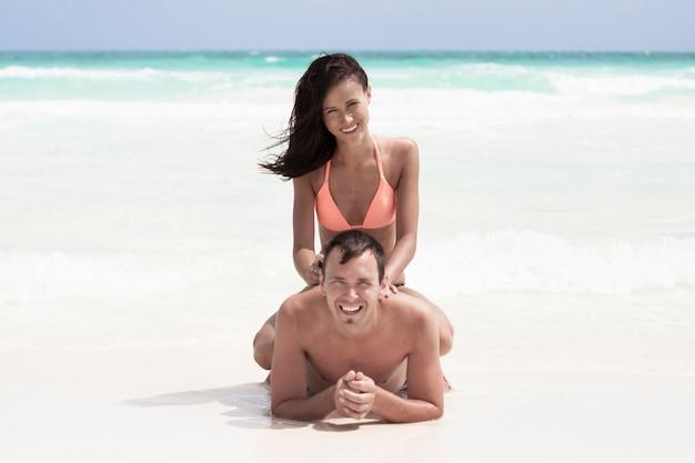 幸せなカップル、ビーチの上に座って