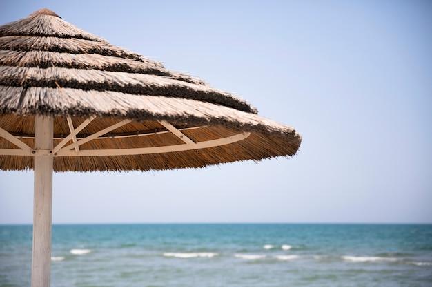 海岸でビーチパラソルを閉じる