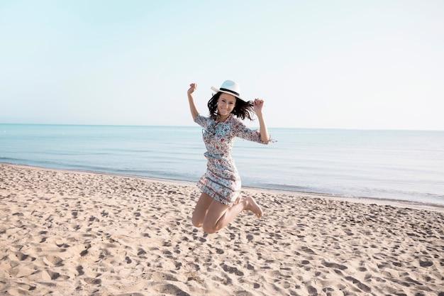 興奮した女性がビーチでジャンプ