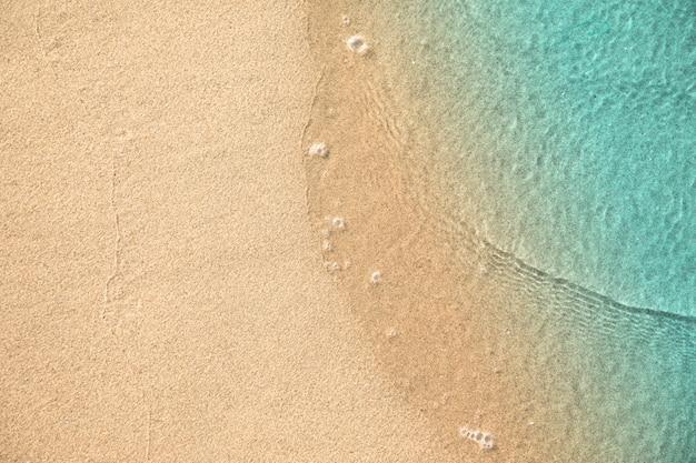 Вид сверху воды касаясь песка на пляже
