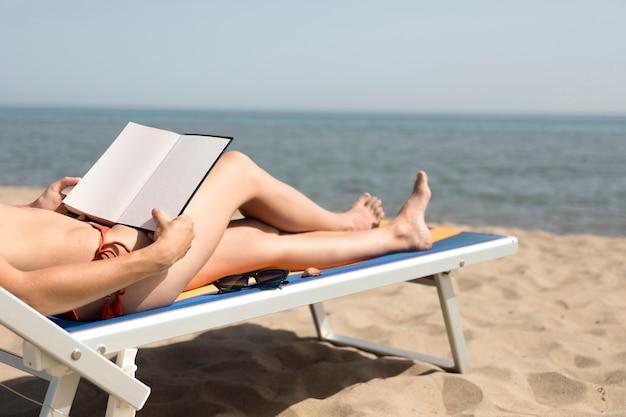 Крупным планом вид сзади женщина на пляже стул чтения