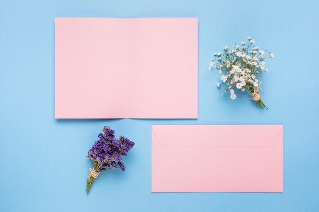 装飾用の花とピンクの結婚式の招待状