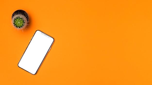 オレンジ色の背景を持つフラットレイアウトモックアップスマートフォン