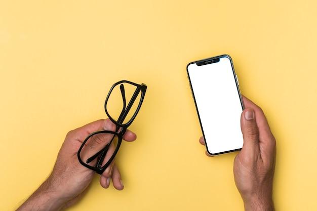 モックアップのスマートフォンを持っているトップビュー人