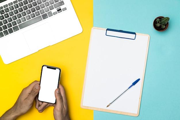 モックアップのスマートフォンとトップビューデスクコンセプト