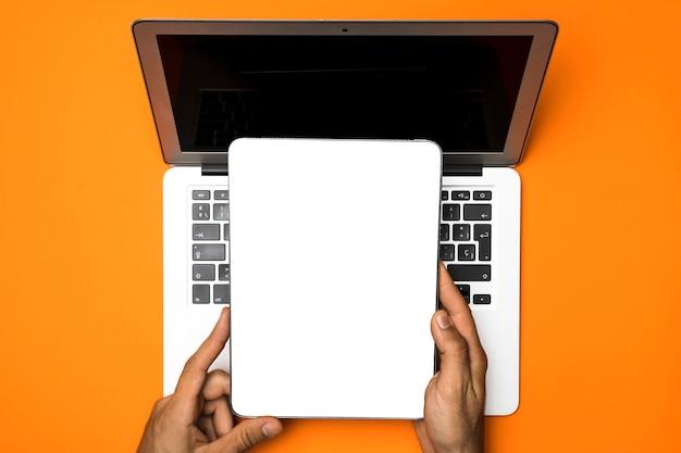 オレンジ色の背景を持つトップビューモックアップタブレット