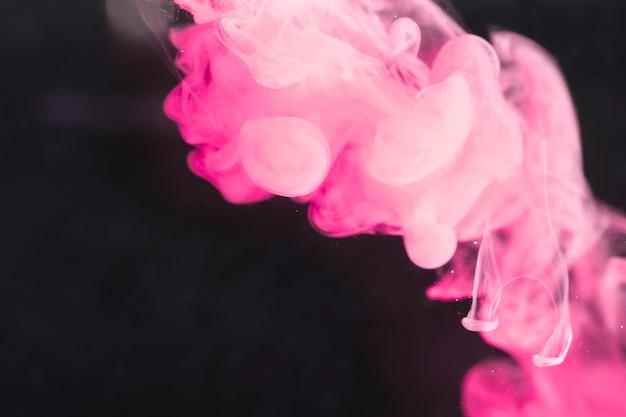 黒い画面に芸術的な強力なピンクの煙