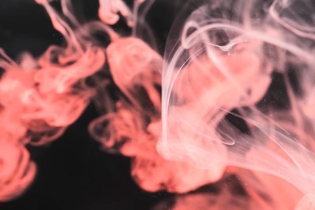黒の背景にピンクの煙