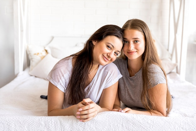 Красивые женщины позируют в спальне