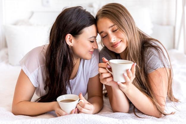 Нежная пара с кофе на кровати