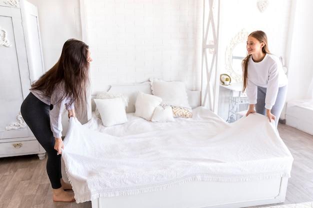 スマイリー女性がベッドを作る