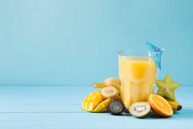 青色の背景においしいフルーツジュース