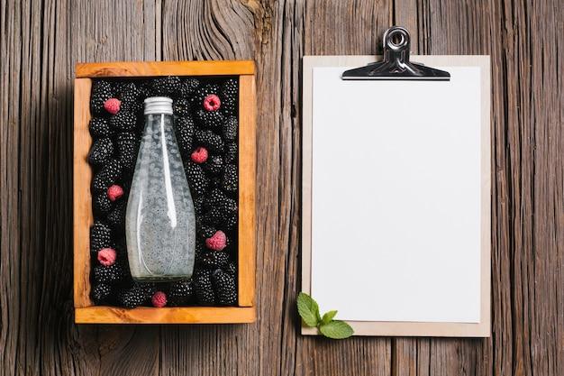 クリップボードと木製の箱にブラックベリージュースの瓶