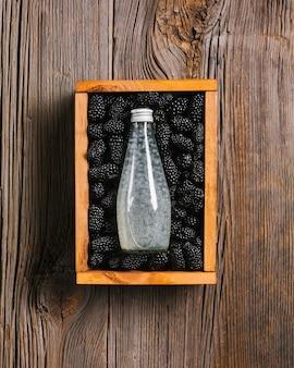 木製の背景にブラックベリージュースの瓶
