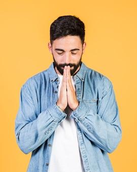 Вид спереди парень молится позиции